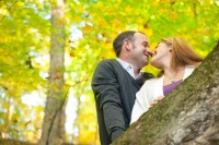 Fall leaves behind engaged couple at Pewitt's Nest in Baraboo, Wisconsin.