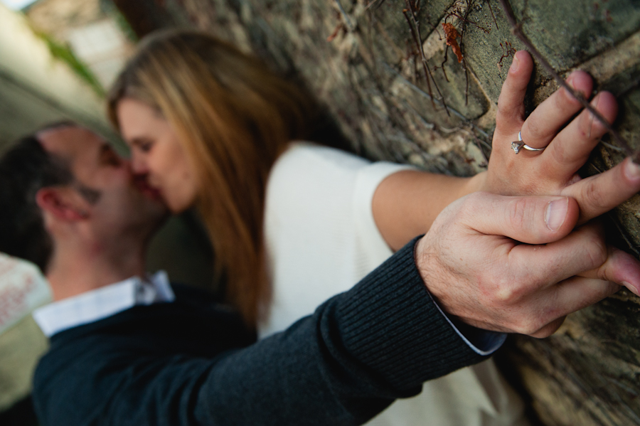 the engagement ring while the couple kisses in the background.