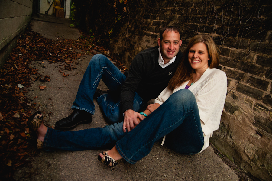 Engaged couple in the back alley with vines and brick.