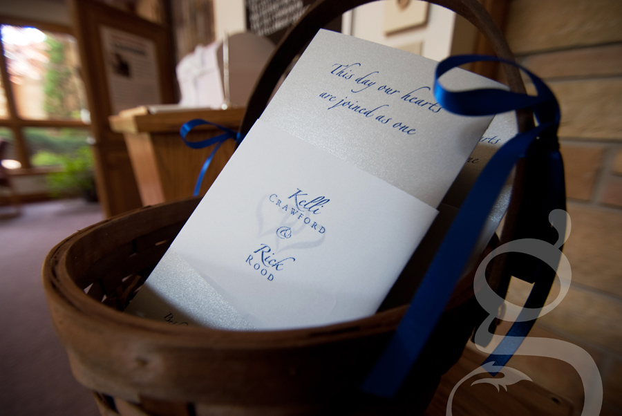 Embossed wedding programs in a basket.