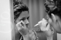 the bride applying her makeup.