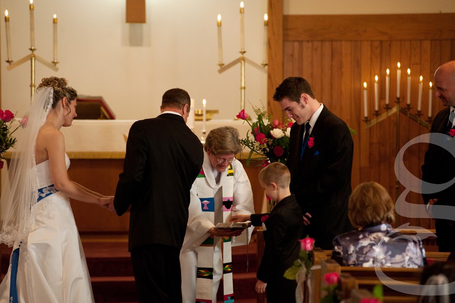 the officiant handing the ring to the ring bearer.