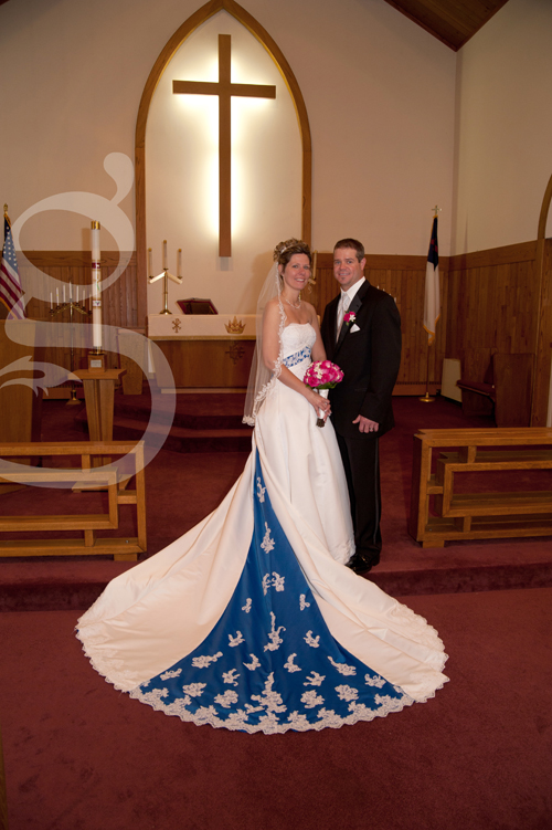 the bride and groom posing in front of the altar in the church.