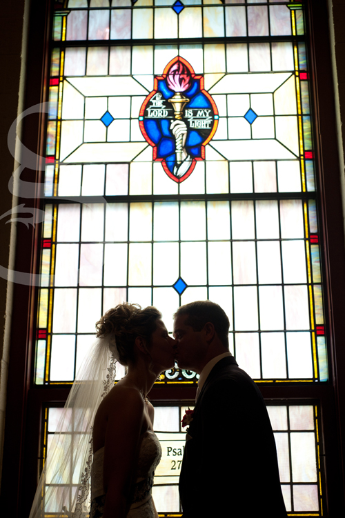 the bride and groom kissing in front of the stained glass window.