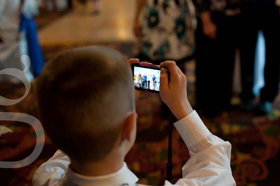 Ring bearer taking pictures at the reception.