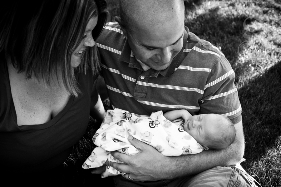 smiling and laughing family with newborn in the back yard.