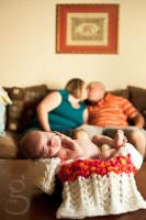 new parents kissing with baby in foreground.