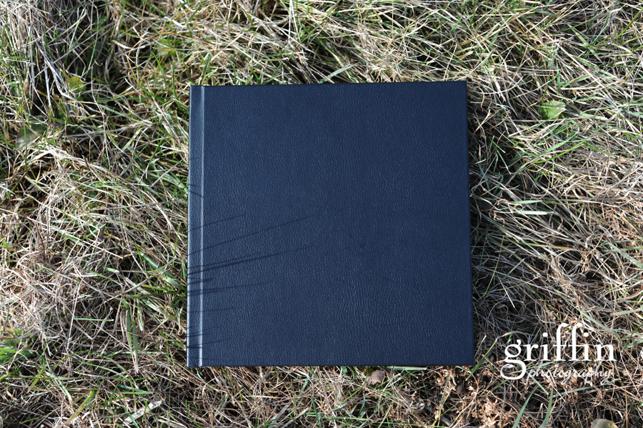 10 inch black leather wedding album laying in the grass