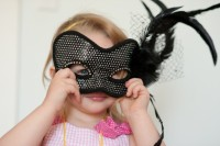 Toddler holding carnival mask up to her face.