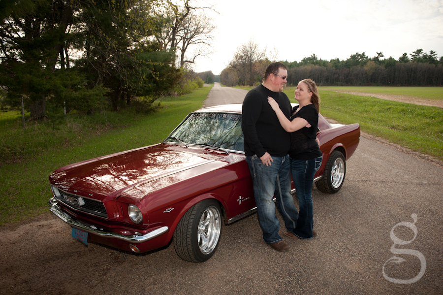Engaged couple next to their 1965 Mustang coupe.