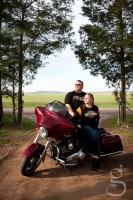 Looking off into the sun while sitting on their Harley.