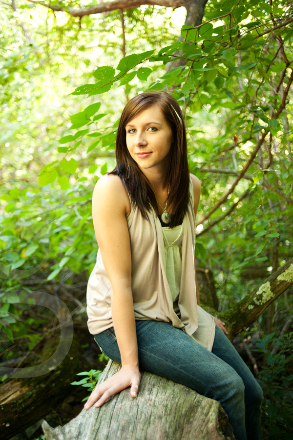 Senior girl seated on a fallen log in front of neon green leaves.