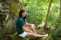 Gymnast seated on mossy rock amidst bluffs for senior portraits.