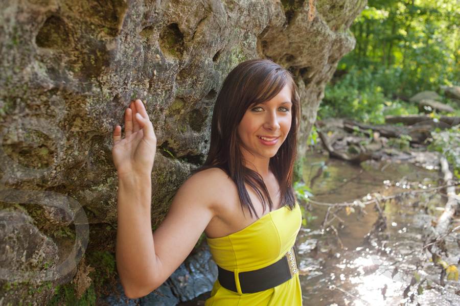 Senior girl in bright yellow dress standing next to pockmarked rock in a creekbed.