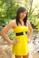 Senior portrait in yellow dress standing in a bubbling brooke.