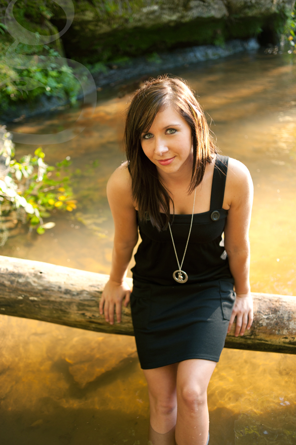 Senior portrait sitting on washed up tree in the middle of the creek at Pewitt's Nest in Baraboo.
