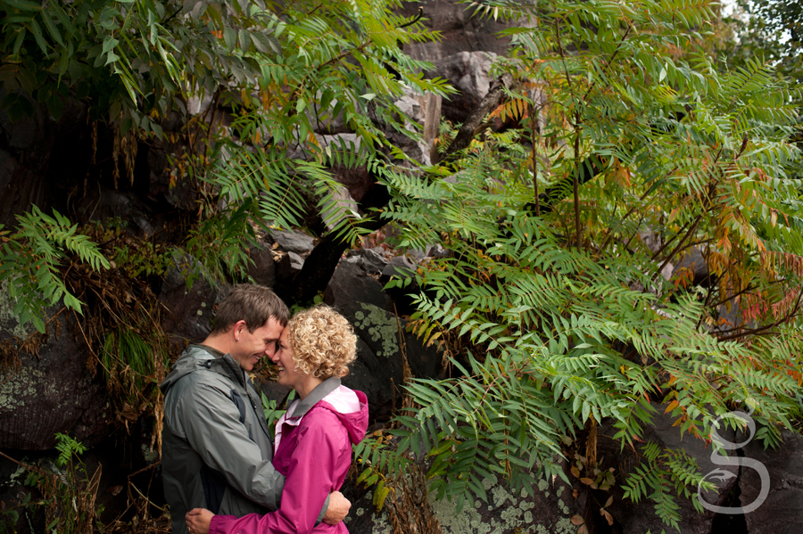 Couple in love nose to nose with dripping wet ferns surrounding them.
