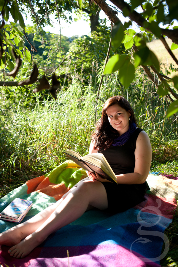 Senior girl reading Harry Potter novel on a quilt under a tree in her black dress.