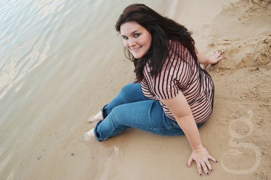 senior girl sitting in the sand with her feet in the lake water in jeans.