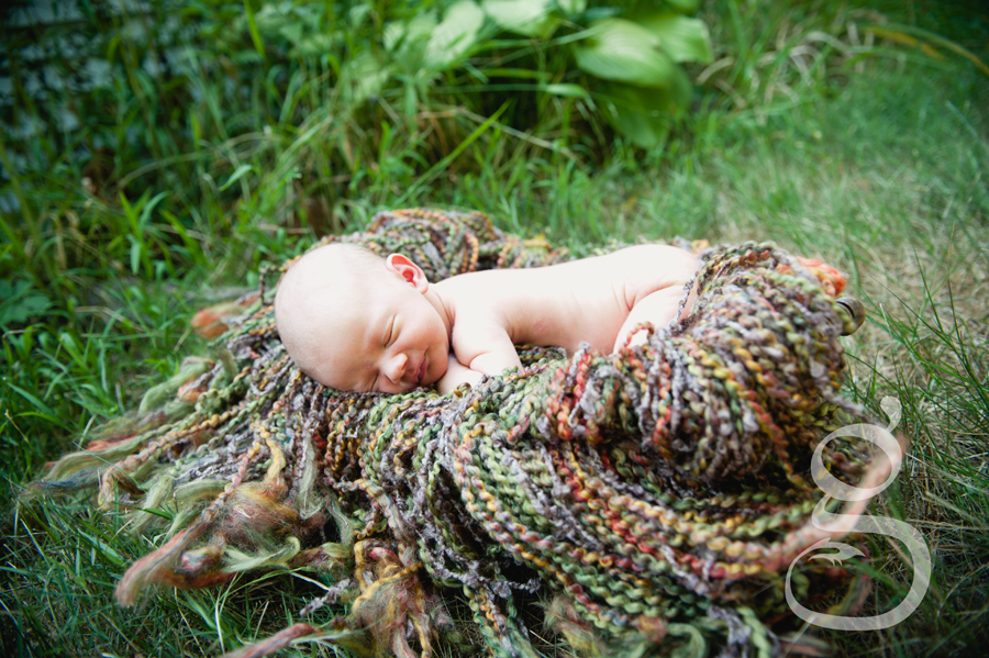 wide shot of sleeping newborn in basket on blanket.