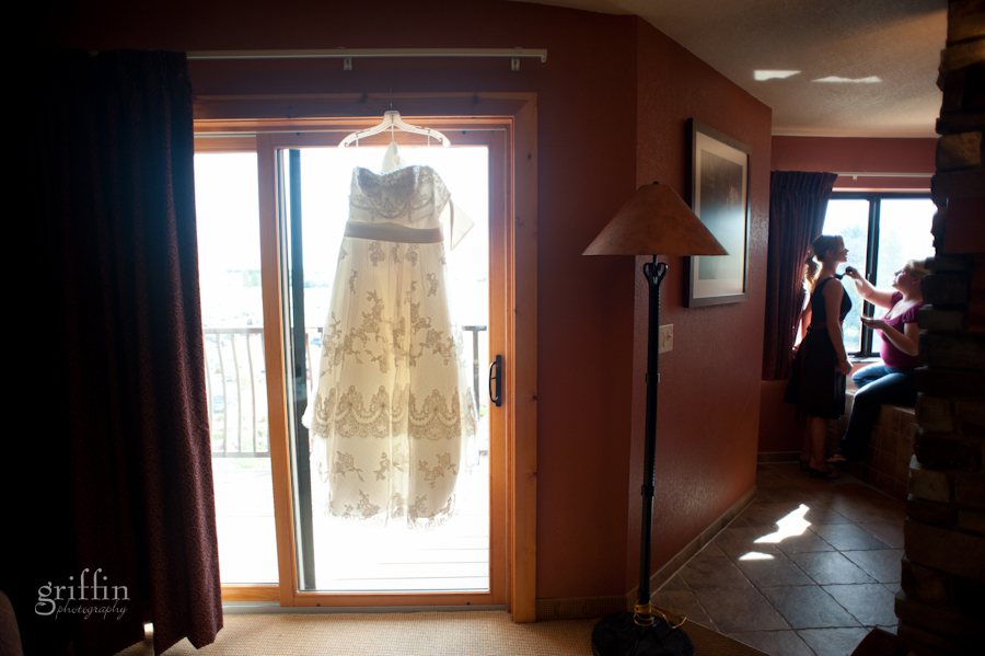 Chula Vista suite with lace wedding dress hanging in doorway and bridesmaide getting make up applied.