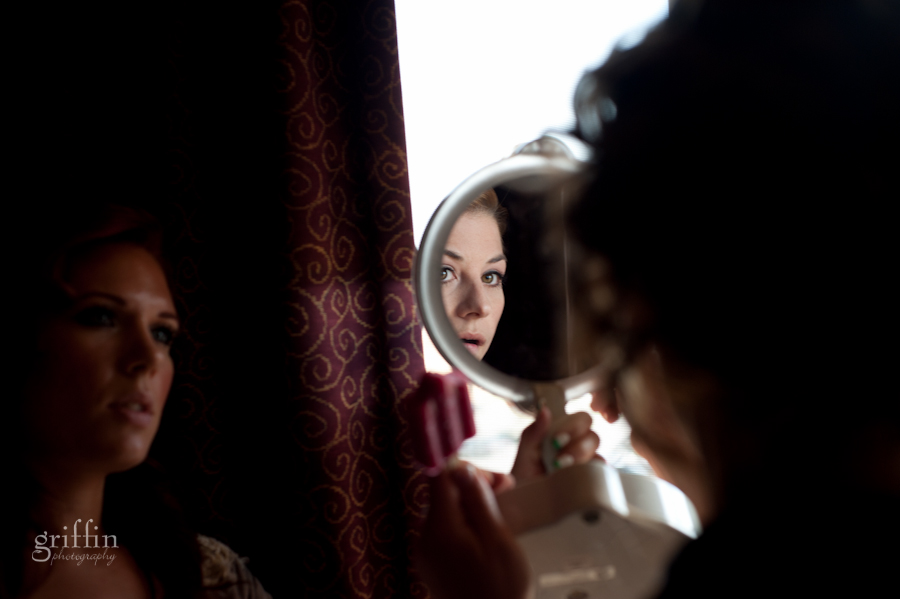 the bride checking out her reflection in the round mirror as the mua looks on.