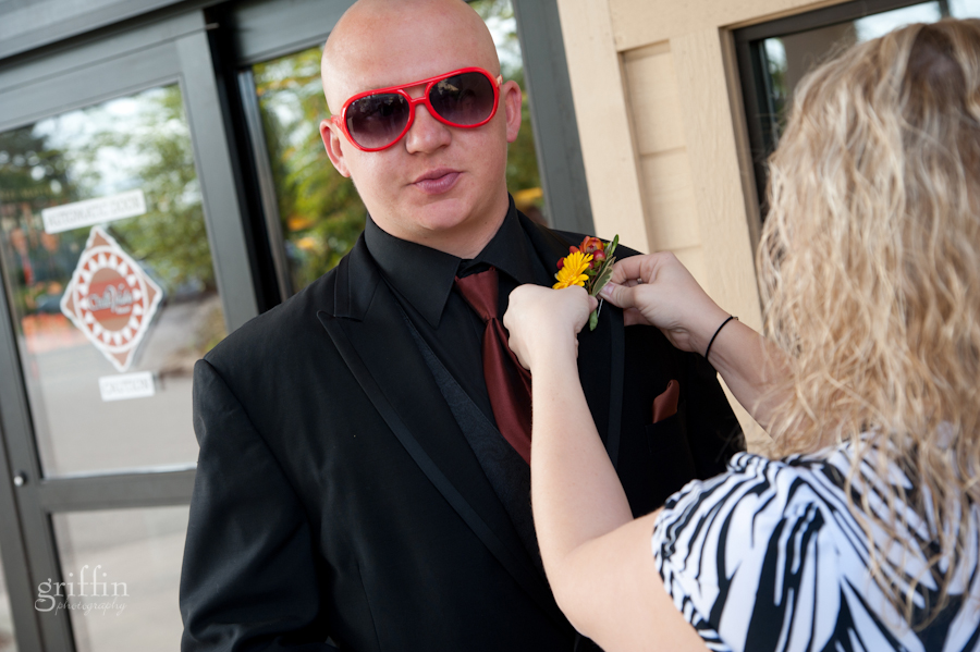 Groom getting his boutonnierre from Wild Apples pinned on while wearing colorful red sunglasses.