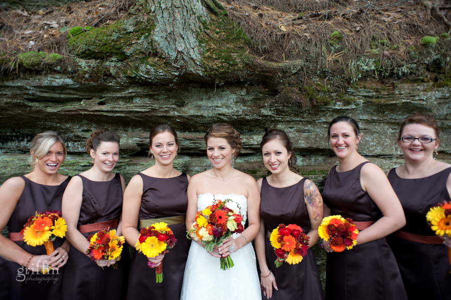 The bride and bridesmaids in their brown dresses standing in front of the rock cliff face.