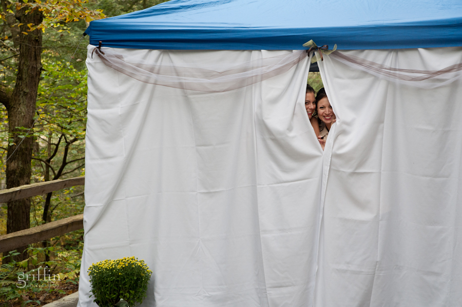A couple of bridesmaid's peeking out of the white tent to check on the guests coming in to the ceremony.