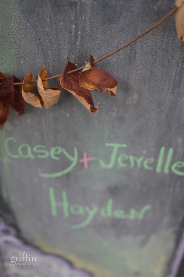 Close up of the chalk door program written by hand and decorated with found leaves and vines.