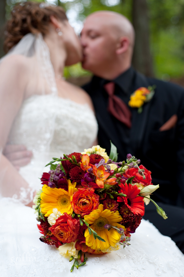 Close up of the bouquet while the bride and groom kiss.