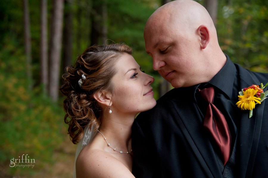 bride and groom nose to nose in front of the towering pines along the Wisconsin River.