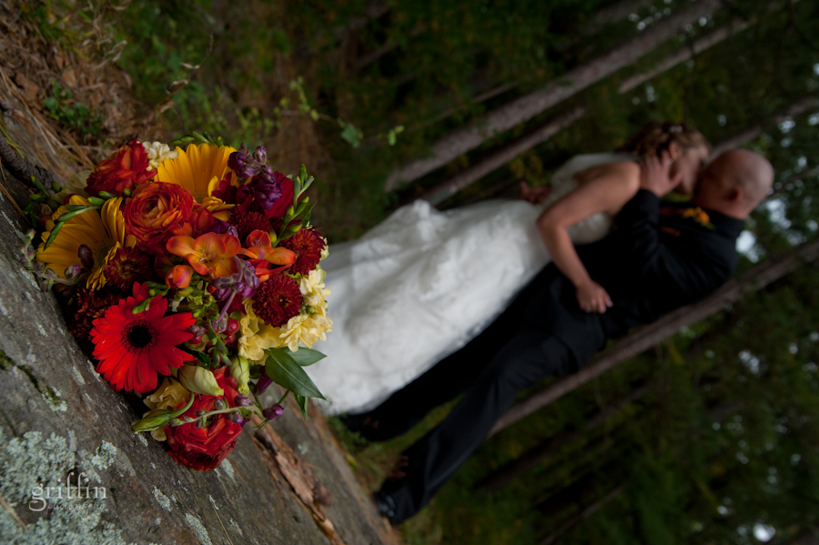 Jenelle and Casey kissing with the bouquet forgotten on the rock before them.
