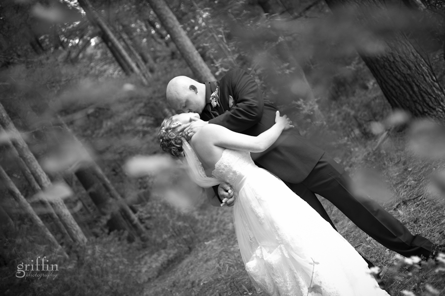 Black and white shot of the bride and groom kissing among the pines.