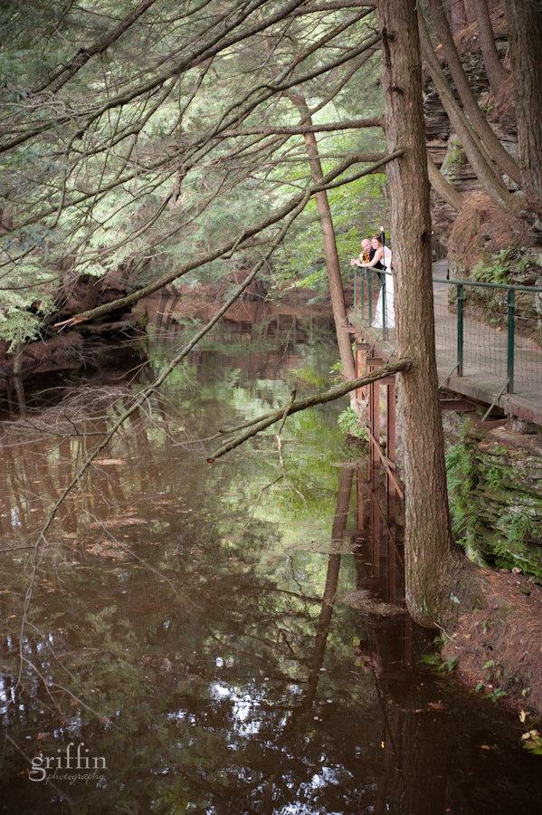 bride and groom standing above the flooded river along the Witche's Gulch trail along the Wisconsin River in the Dells.