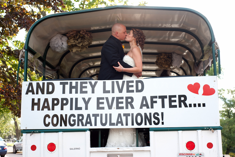 """Original Wisconsin Duck with the bride and groom kissing in front of """"happily ever after"""" sign."""