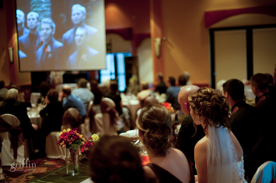 the bridal party watching the wedding day video on the pull down screen.