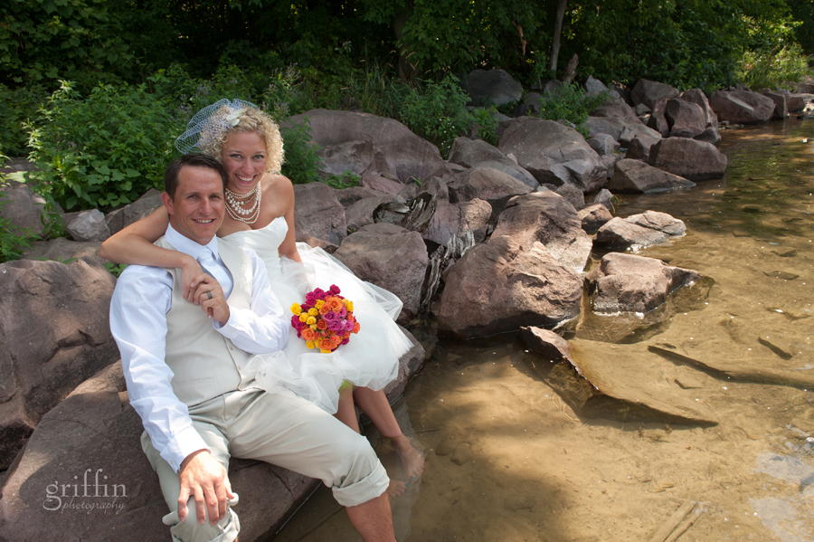 Laura and Josh with their feet in the water at Devil's Lake on their wedding day.