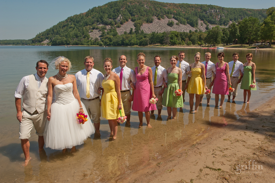 the super colorful bridal party standing in Devil's Lake in their formal wear.