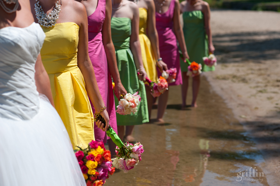 bridesmaid dresses in yellow, pink and green with their bouquets.