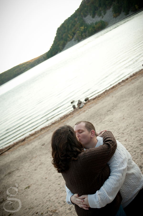 Monica and Shaun kissing in front of Devil's Lake.