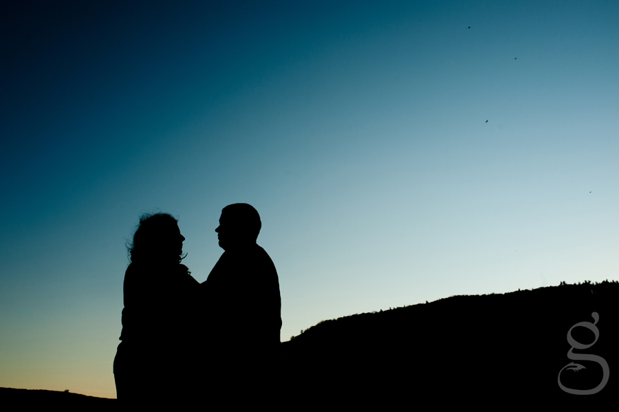 Silhouette of engaged couple with the Baraboo bluffs behind them at Devil's Lake.