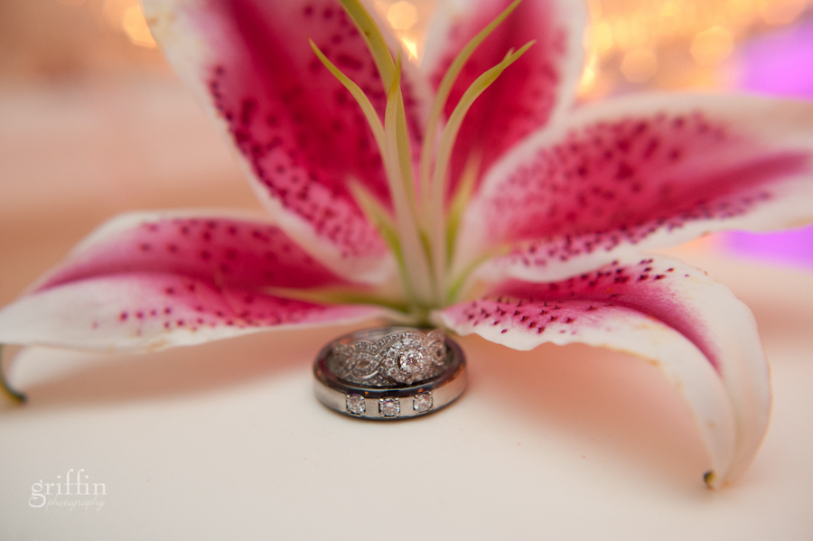 Wedding rings in front of stargazer lily.