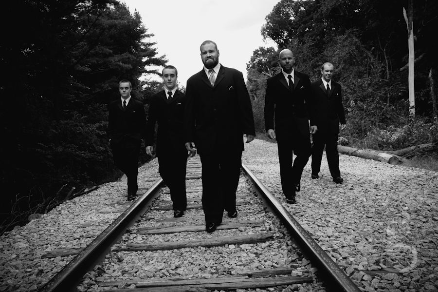 black and white shot of the groom and groomsmen walking down the railroad tracks.