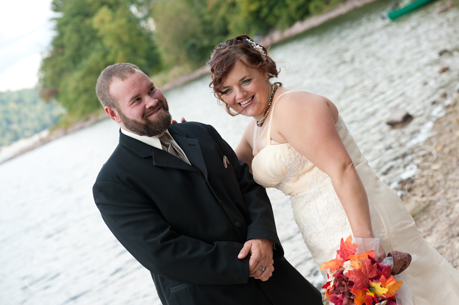 bride and groom laughing with Devil's Lake in the background.
