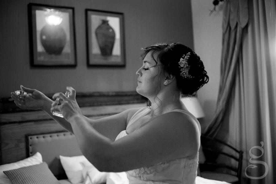 the bride applying her perfume in the hotel room before the ceremony.