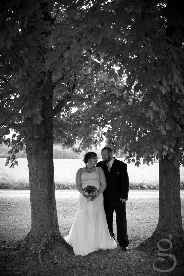 black and white shot at the couple's home between two tall trees.