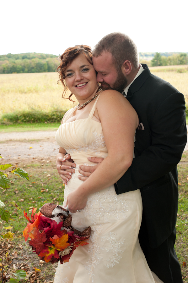 Groom kissing his bride's neck along a back country road.