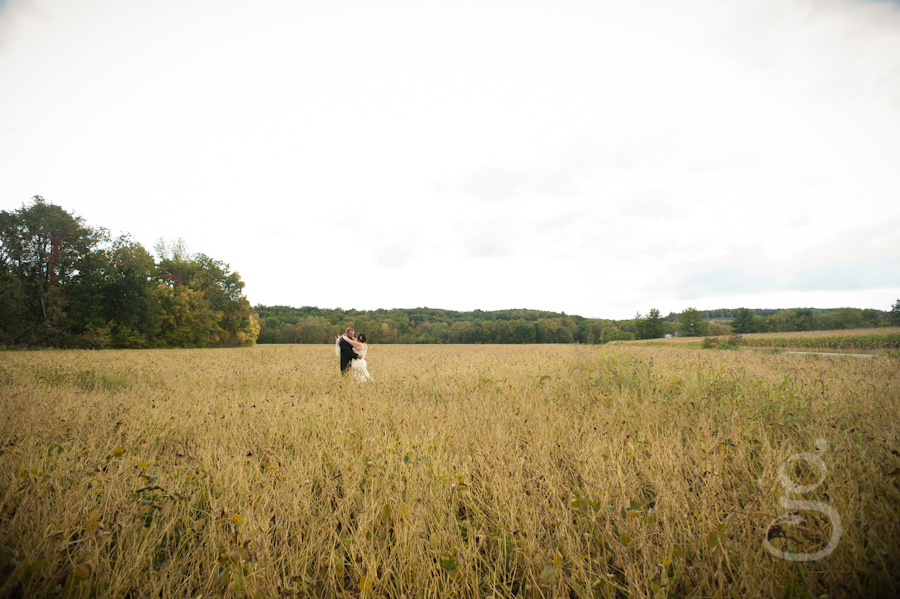 bride and groom hugging in the center of the wheat field.
