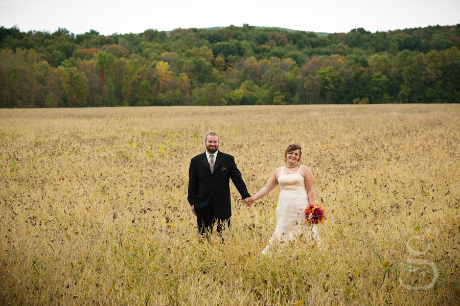 Scott and Harmony looking at the camera in the center of the wheat field with bluffs behind them in the background with fall colors.